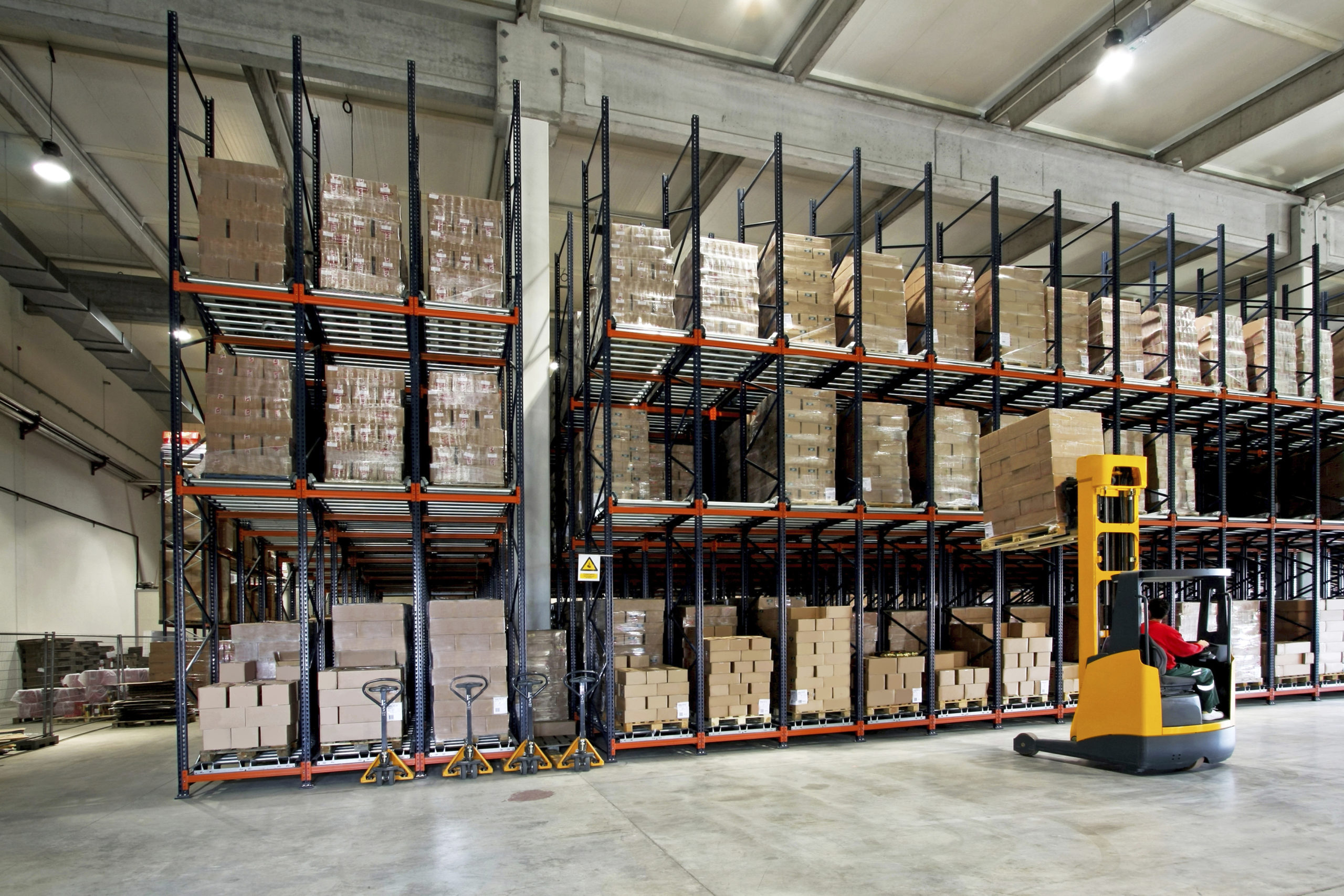 Forklift delivering boxes in manufacturing warehouse.